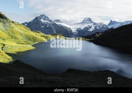 Picturesque view on Bachalpsee lake in Swiss Alps mountains. Snowy peaks of Wetterhorn, Mittelhorn and Rosenhorn on background. Switzerland - Stock Photo