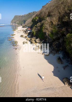 Indonesia, Bali, Aerial view of Karma Kandara beach, man walking on beach