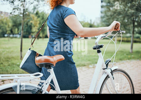 Young woman walking in park, pushing bicycle