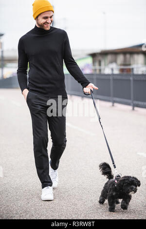 Fashionable young man walking with dog on a bridge - Stock Photo