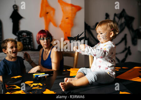Baby girl playing with halloween decoration at home while mother and brother watching her - Stock Photo