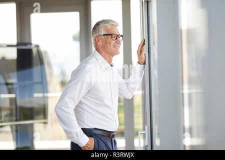 Confident businessman standing in office, looking out of window - Stock Photo