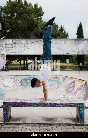 Young man doing a handstand on bench in skatepark Stock Photo