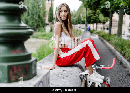 Smiling teenage girl with cell phone sitting on a wall at the riverside next to bicycle - Stock Photo