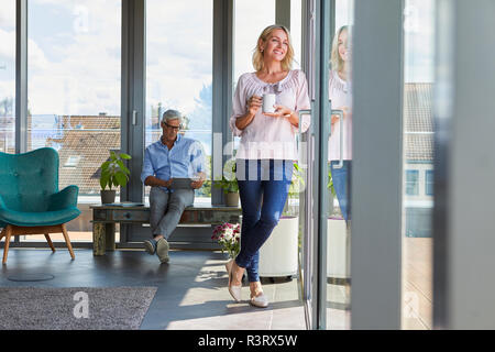 Smiling mature couple relaxing at home with woman looking out of window and man using tablet - Stock Photo