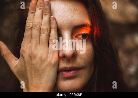 Portrait of young woman with freckles covering one eye - Stock Photo