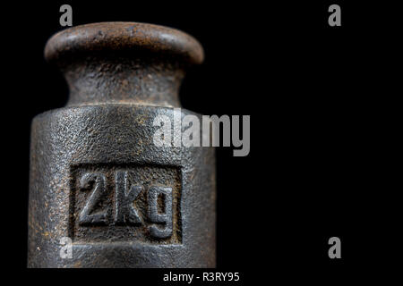 A kilogram weight used for weighing a given quantity in the store. Weights of one kilogram and two kilograms. Dark background. - Stock Photo