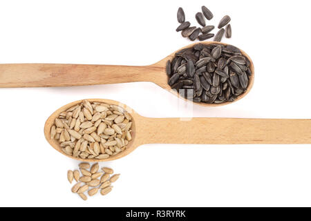 peeled and unpeeled seeds in a wooden spoon isolated on white background. Top view - Stock Photo