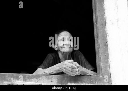 Boca de Valeria, Brazil - December 03, 2015: old mature mulatto woman with kind smiling face holding hands together standing in wooden window brown an - Stock Photo