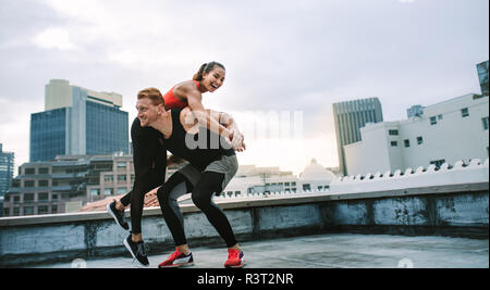 Man lifting a woman athlete on his back during fitness training on rooftop. Fitness man and woman in cheerful mood having fun during workout on terrac - Stock Photo