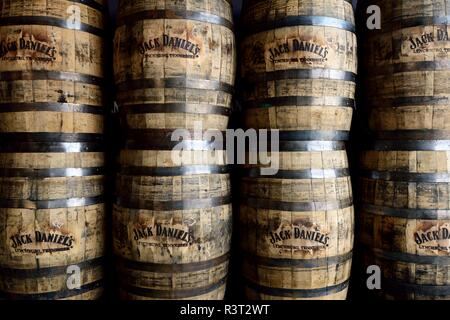 Stacked rows of wooden Jack Daniels aged oak whiskey barrels - Stock Photo