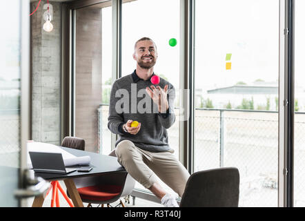 Smiling young businessman sitting at the window juggling with balls - Stock Photo