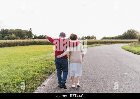 Senior couple on a walk in rural landscape - Stock Photo