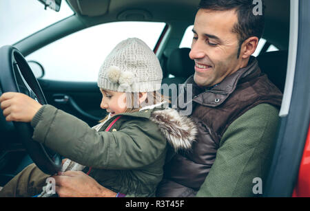 Happy little girl with wool cap driving car sitting on father's lap - Stock Photo