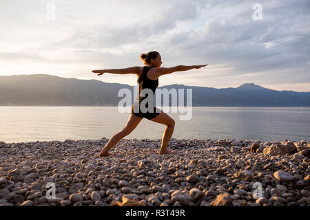 Young woman doing yoga at the stony beach in the evening, Warrior pose - Stock Photo