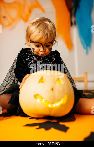 Portrait of little girl with painted face and fancy dress sitting on table with Jack O'Lantern pouting mouth - Stock Photo