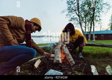 Sweden, Lapland, Two friends preparing a bonfire at the lakeshore - Stock Photo