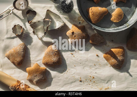 Christmas Cookies and cookie cutters on baking paper - Stock Photo