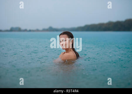 Portrait of smiling young woman  bathing in lake on rainy day - Stock Photo