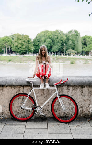 Teenage girl with cell phone sitting at the riverside next to bicycle - Stock Photo