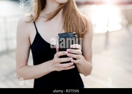 Young woman holding cup of coffee - Stock Photo