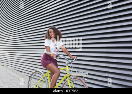 Portrait of smiling young woman riding bicycle - Stock Photo