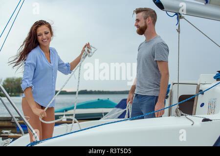 Couple unmooring sailing boat - Stock Photo