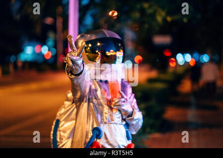 Spaceman in the city at night with takeaway drink making victory gesture - Stock Photo