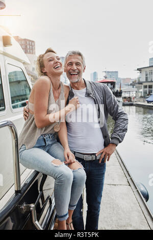 Laughing older man and young woman standing on jetty next to yacht - Stock Photo