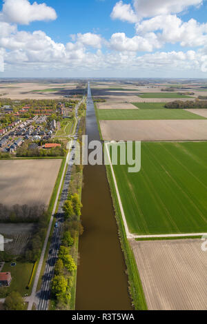 Long straight canal next to road, near Amsterdam, North Holland, Netherlands - Stock Photo