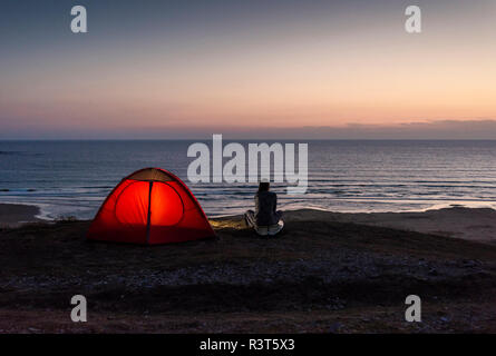 Young woman sitting by tent, looking at the sea at night - Stock Photo