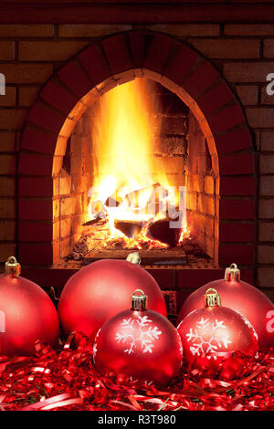 red Xmas baubles and tinsel with home fireplace - Stock Photo