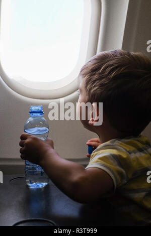 Little boy in an airplane looking out of window - Stock Photo