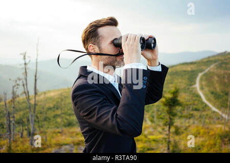 Businessman looking through binoculars on top of a mountain - Stock Photo