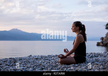 Young woman doing yoga at the stony beach in the evening, meditation - Stock Photo