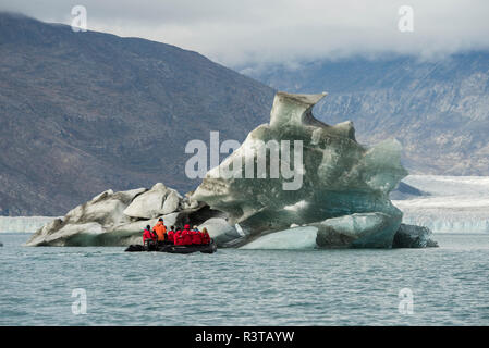 Eastern Greenland, Scoresbysund, aka Scoresby Sund. Adventure tourists in zodiac exploring iceberg at Wilson glacier. (For Editorial Use Only) - Stock Photo