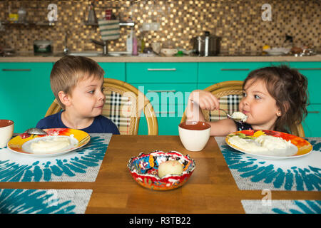 Portrait of boy and his little sister eating breakfast in the kitchen - Stock Photo