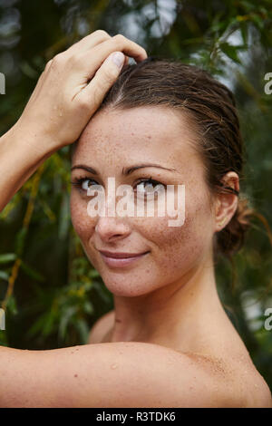 Portrait of freckled young woman in nature - Stock Photo