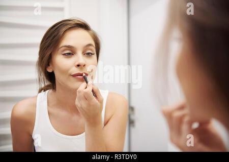 Mirror image of young woman in bathroom applying lipliner - Stock Photo