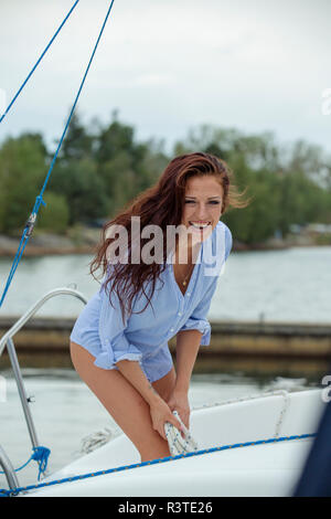 Woman on sailing boat holing rope, laughing - Stock Photo