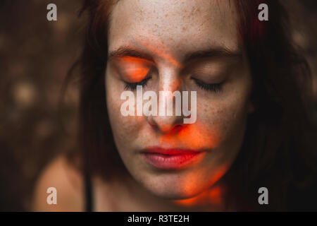 Portrait of young woman with freckles closing her eyes - Stock Photo