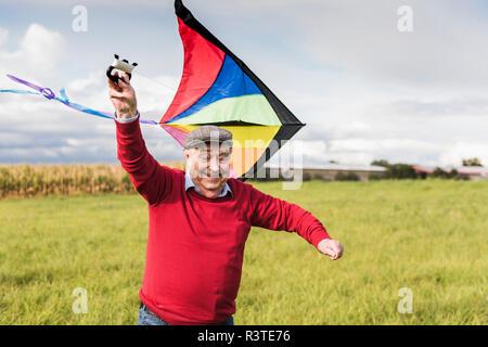 Happy senior man flying kite in rural landscape - Stock Photo