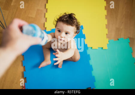 Father's hand giving baby boy a bottle of water Stock Photo
