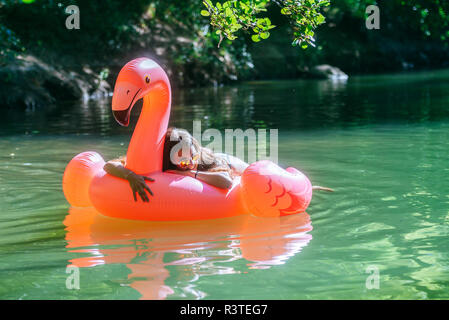 Woman floating on water on an inflatable flamingo - Stock Photo