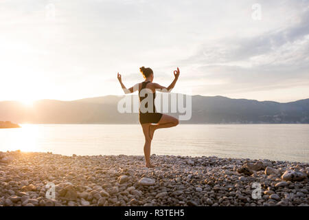 Young woman doing yoga on a stony beach at sunset, tree position - Stock Photo