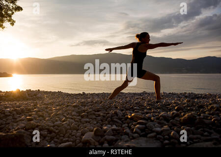 Young woman doing yoga at the stony beach at sunset, Warrior pose - Stock Photo