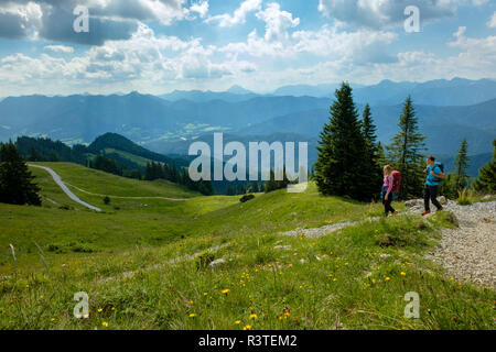 Germany, Bavaria, Brauneck near Lenggries, young couple hiking in alpine landscape - Stock Photo