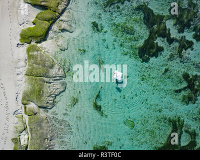 Indonesia, Bali, Aerial view of Karma Kandara beach, one woman, airbed floating on water - Stock Photo