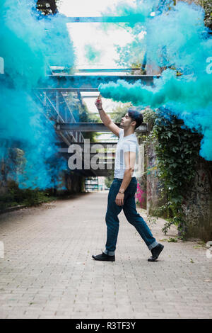 Young man walking with smoke torch outdoors Stock Photo