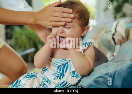 Mother taking temperature of her crying baby girl - Stock Photo